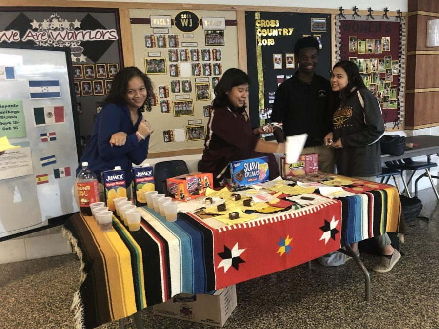 Seniors Kariya Spencer and Lorena Vicenteno work with freshmen Christian Tucker and Sarah Ortega at cultural taste testing event to celebrate Hispanic Heritage Month and diversity at WJ.