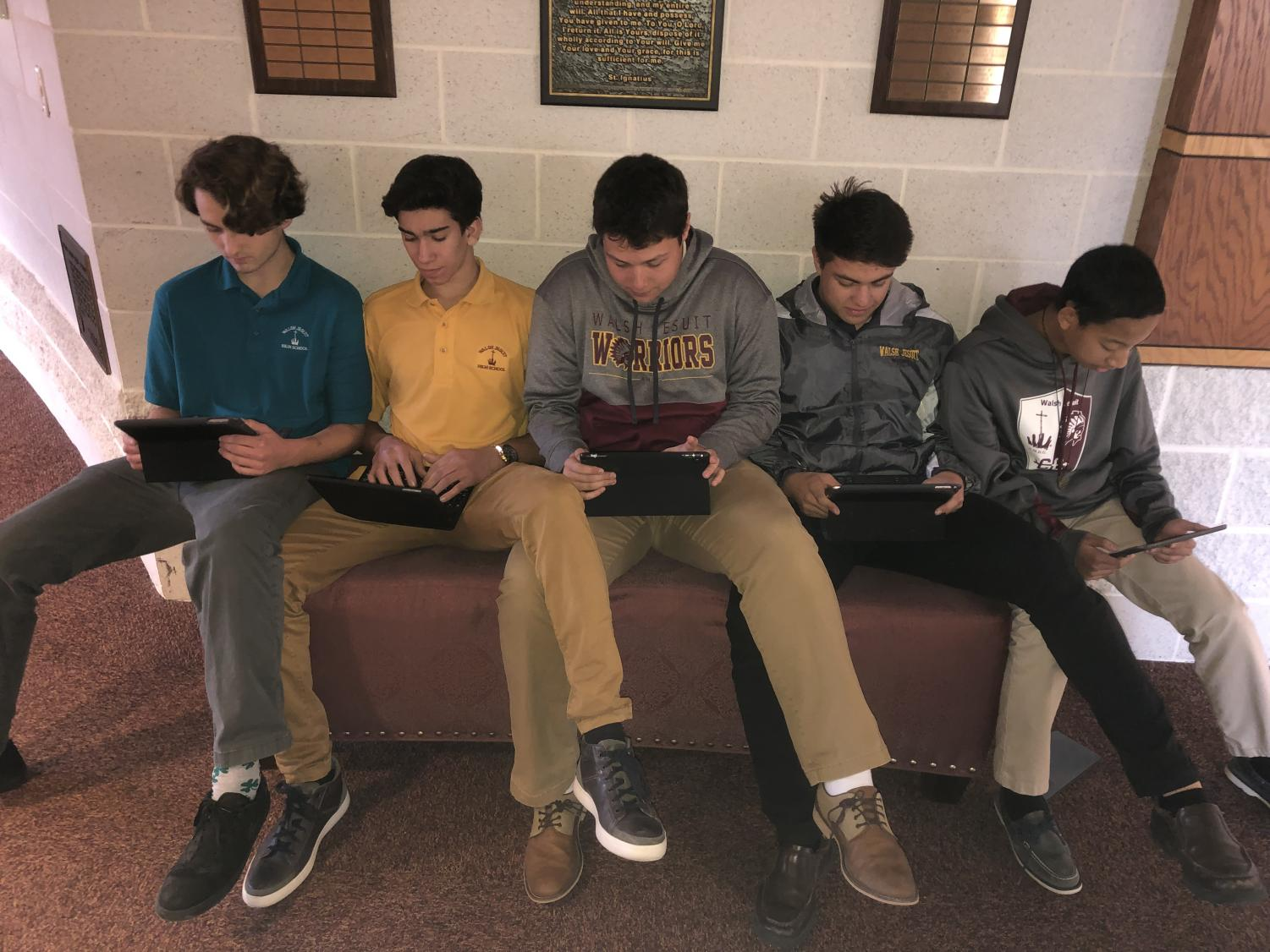 These juniors, like many others, pile up along the hallway by the business offices leading to the Chapel to use their iPads.
