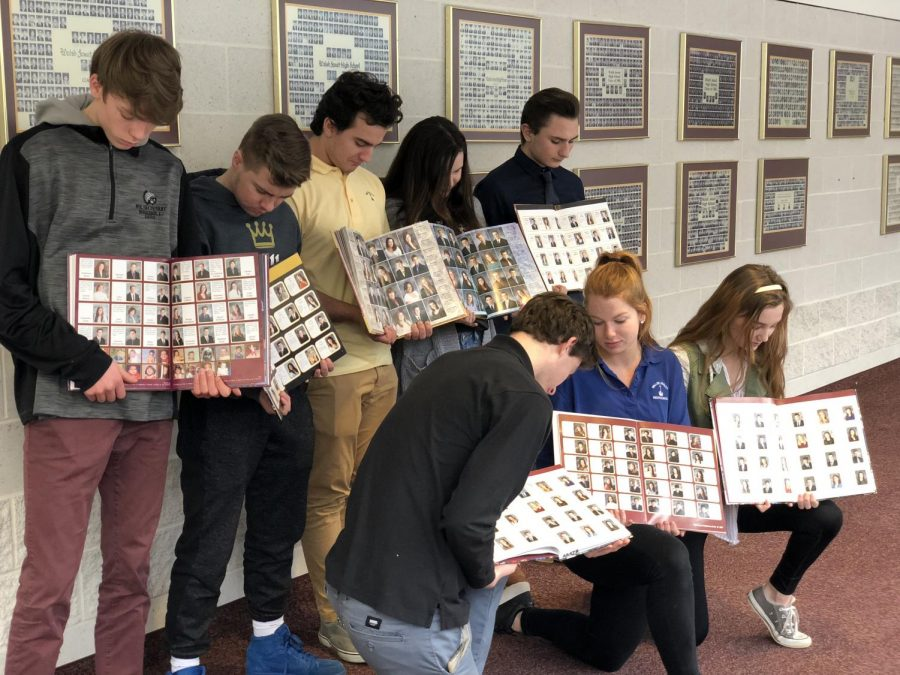 Seniors pose with old yearbooks opened to the senior section which feature unique quotes for each student.