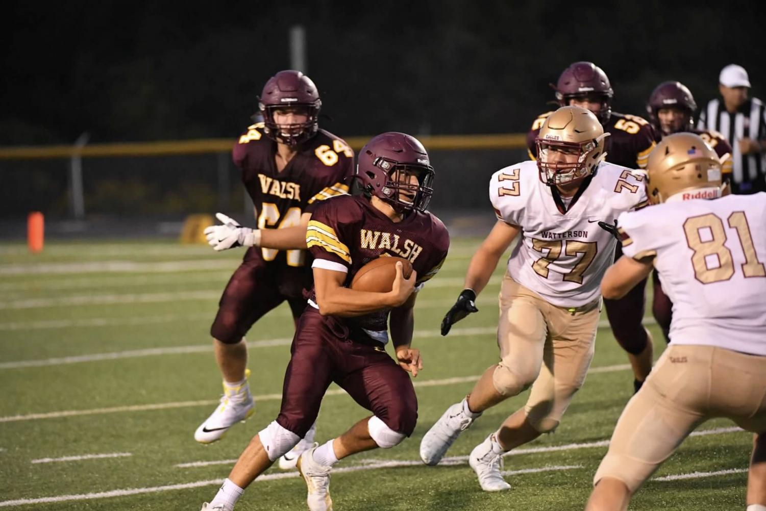Senior quarterback Cam Mayes runs the ball for the Warriors against Bishop Watterson.