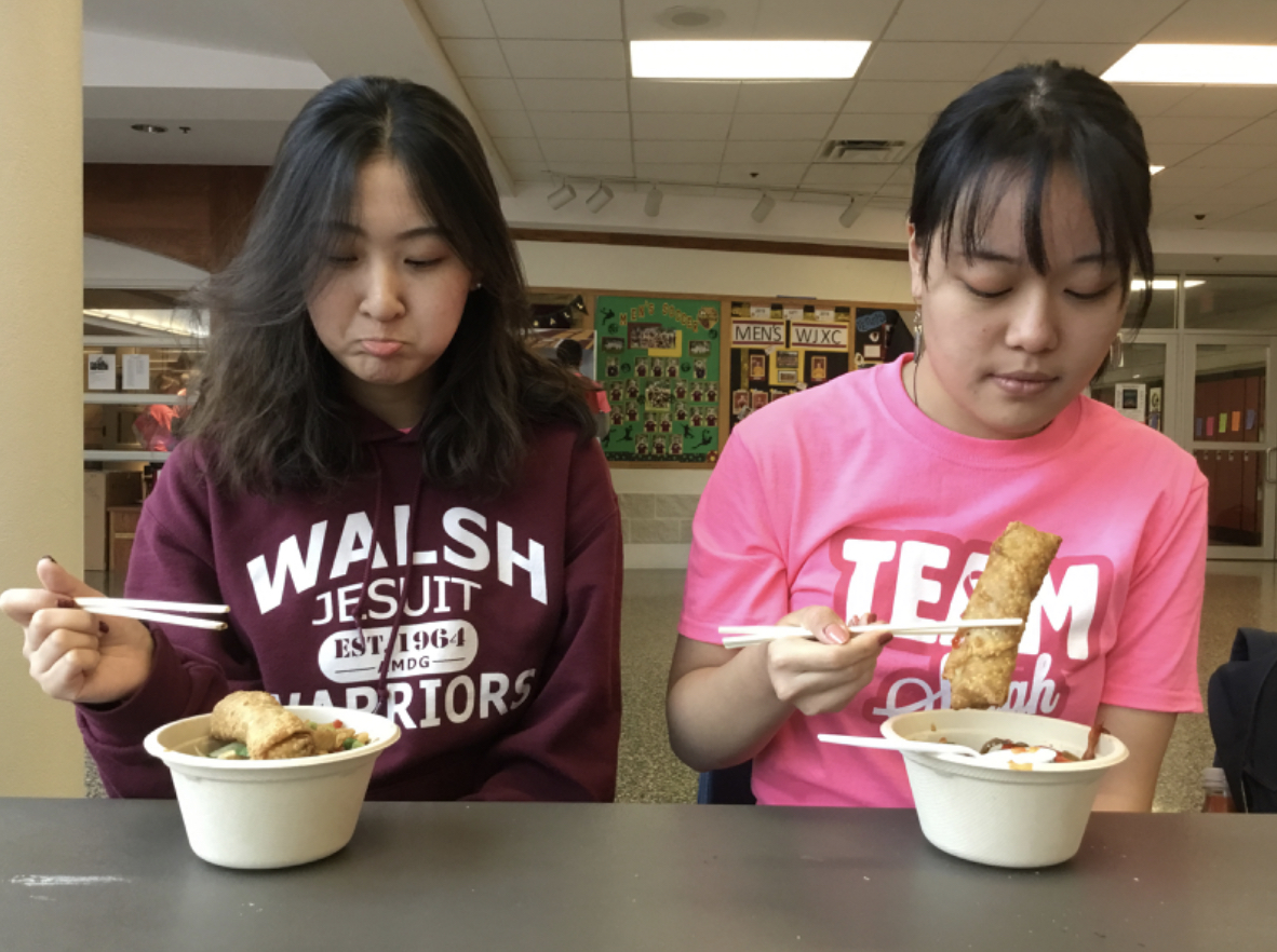 Seniors Jancy Zhang (left) and Phyllis Liu sit down with mixed reactions as they prepare to eat a meal with with chopsticks.