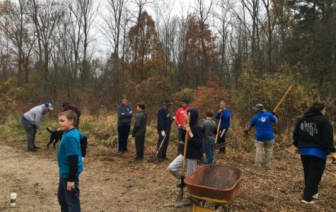 Troop 334's scouts and their families fill wheelbarrows with mulch.