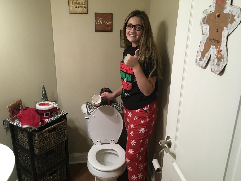 Junior Mia DeSciscio dumps a mug of ice cubes into the toilet in hopes of a snow day.