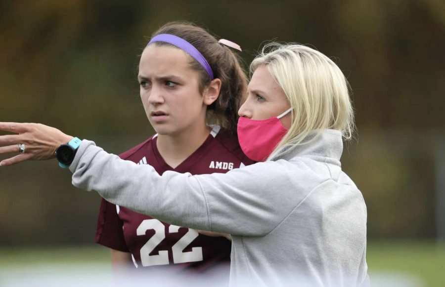 Mrs. Brittany Eismon, a junior varsity coach, points out a new strategy on the field to junior Grace Iero.