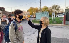 Every morning all students and adults of Walsh Jesuit are required to have a temperature check before entering the building. Mrs. April Katona, secretary to the principal, checks Jimmy Taylor '23.